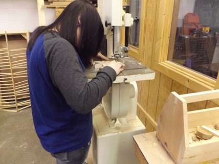 Student cutting wood for project