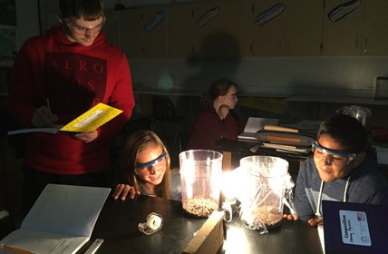 Students view light bulb between two beakers in darkened room.